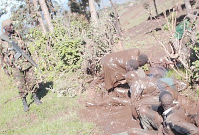 An army officer stands guard as a group of people swim in the mud in Mt Elgon. They do not appear like they are doing it willingly though. Picture by the Standard newspaper.