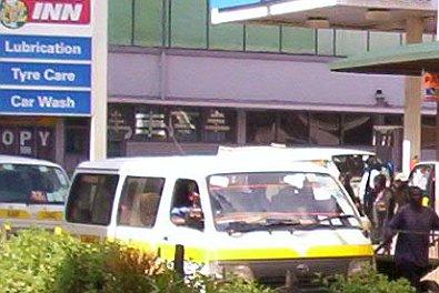 Public transport vehicles (matatus) at a Nairobi fuel station.