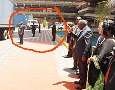 President Mwai Kibaki (right) surrounded by heavy security (left) at a government function in Nairobi.