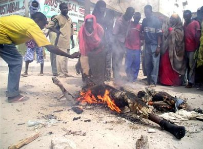 Mogadishu residents converge around the body of a government soldier who caught fire during intense fighting.